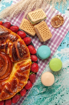 Draufsicht köstliche torte mit macarons waffeln und frischen roten erdbeeren auf blauem schreibtisch