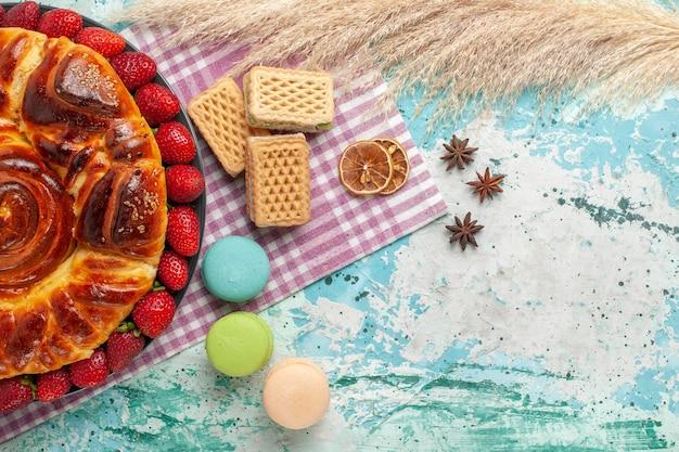 Draufsicht köstliche torte mit macarons waffeln und frischen roten erdbeeren auf blauer oberfläche