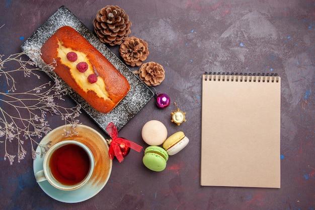 Draufsicht köstliche torte mit tasse tee auf dem dunklen hintergrund kuchen zuckerplätzchen-torte süßer keks-tee
