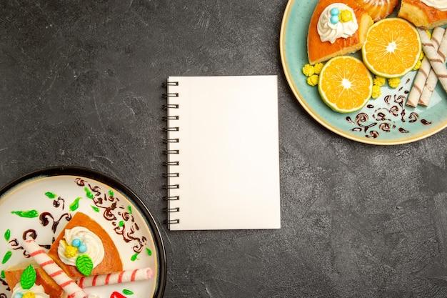Draufsicht köstliche tortenscheiben mit frischen mandarinen auf grauem hintergrund tortenfrucht-süßigkeiten-teig-teekuchen