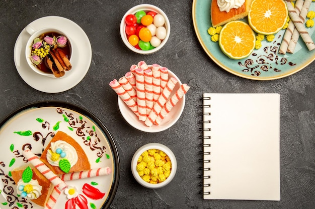 Draufsicht köstliche tortenscheiben mit frischen mandarinen und tasse tee auf dunkelgrauem hintergrund torte obst süßigkeiten kuchen teig tee cake