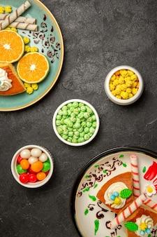 Draufsicht köstliche tortenscheiben mit geschnittenen mandarinen auf dunkelgrauem hintergrund obstsüßigkeiten kuchen tortenteig tee