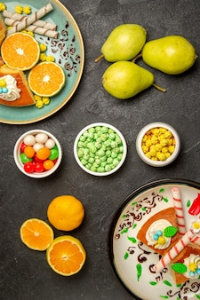 Draufsicht köstliche tortenscheiben mit geschnittenen mandarinen und birnen auf dunkelgrauem hintergrund obstsüßigkeiten kuchen tortenteig tee