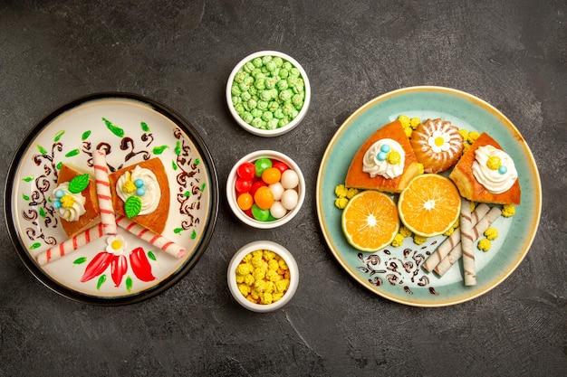 Draufsicht köstliche tortenscheiben mit mandarinen und bonbons auf dem dunkelgrauen hintergrund obst-süßigkeiten-kuchen-torten-teig-tee