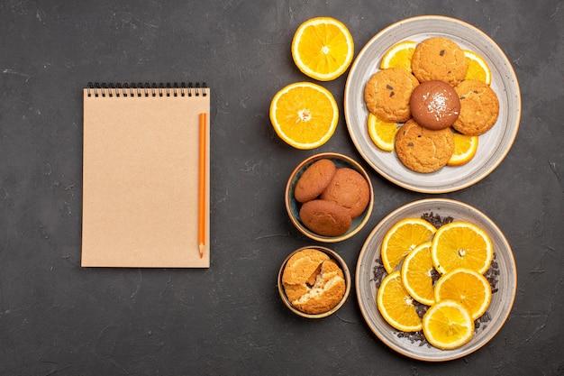 Draufsicht köstliche zuckerkekse mit frisch geschnittenen orangen auf dem dunklen hintergrund zuckerkeks süßer keksfruchtkuchen