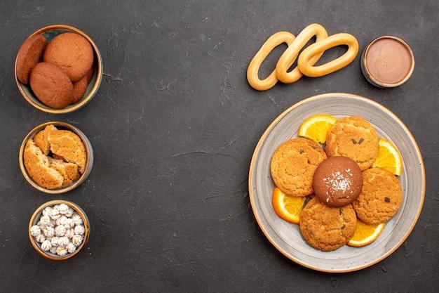 Draufsicht köstliche zuckerkekse mit frisch geschnittenen orangen auf dunklem hintergrund cookie keks zuckerkuchen dessert süß