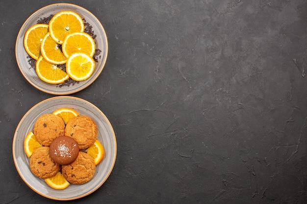 Draufsicht köstliche zuckerkekse mit frisch geschnittenen orangen auf dunklem hintergrund zuckerkeks süße kekse frucht