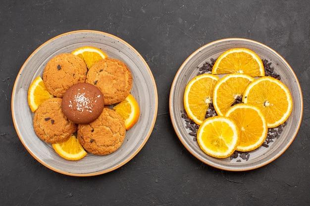 Draufsicht köstliche zuckerkekse mit frisch geschnittenen orangen auf dunklem hintergrund zuckerkeks süße keksfrucht