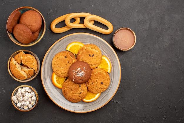 Draufsicht köstliche zuckerkekse mit frisch geschnittenen orangen auf dunklem schreibtischplätzchen-keks-zuckerkuchen-dessert süß