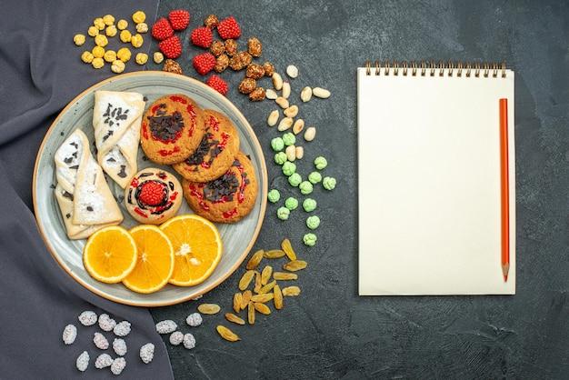 Draufsicht köstliche zuckerkekse mit gebäck und orangenscheiben auf der dunklen oberfläche zuckerkeks süße kekse kuchentee