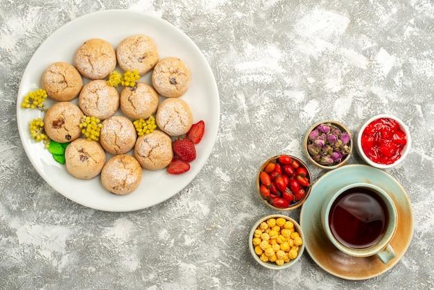 Draufsicht köstliche zuckerkekse mit tasse tee auf der weißen oberfläche kekskekszuckerkuchen süßer tee