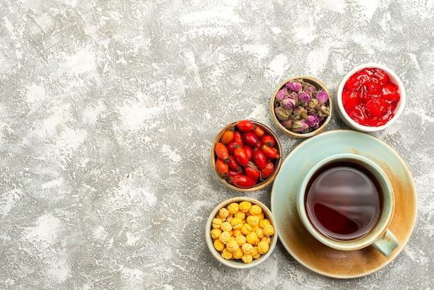 Draufsicht köstliche zuckerkekse mit tasse tee auf weißem hintergrund kekse kekszuckerkuchen süßer tee