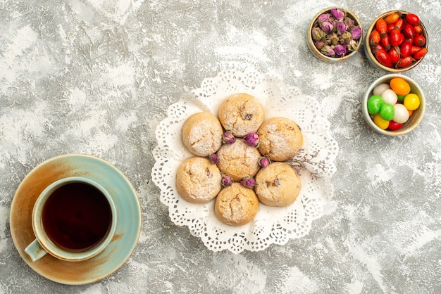 Draufsicht köstliche zuckerkekse mit tasse tee auf weißer oberfläche kekszuckerplätzchen süßer teekuchen