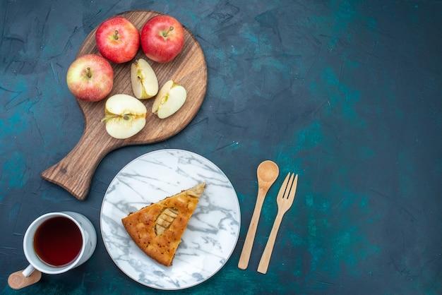 Draufsicht köstlicher apfelkuchen in innenplatte mit tee und äpfeln auf dunkelblauem schreibtisch obstkuchen kuchen zucker süß geschnitten