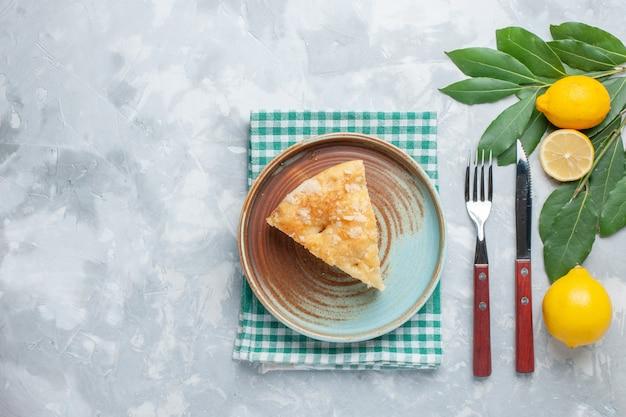 Draufsicht köstlicher apfelkuchen in innenplatte mit zitronen auf leichtem schreibtischkuchenkuchen süßer backkeks geschnitten