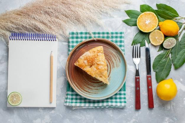 Draufsicht köstlicher apfelkuchen in innenplatte mit zitronen auf leichtem schreibtischkuchenkuchen süßer keks geschnitten
