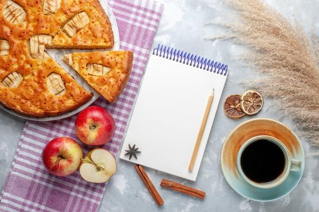 Draufsicht köstlicher apfelkuchen innerhalb platte mit äpfeln notizblock und tasse tee auf hellem hintergrund kuchen kekskuchen süß