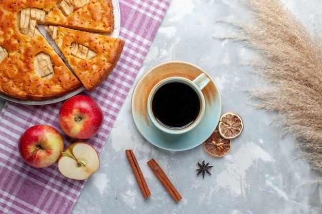 Draufsicht köstlicher apfelkuchen innerhalb platte mit äpfeln und tasse tee auf leichtem schreibtischkuchenkeks süß