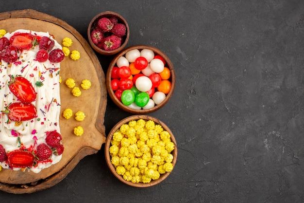 Draufsicht köstlicher cremiger kuchen mit früchten und bonbons auf dunklem hintergrund keks-tee-plätzchenkuchen süße sahnesüßigkeit
