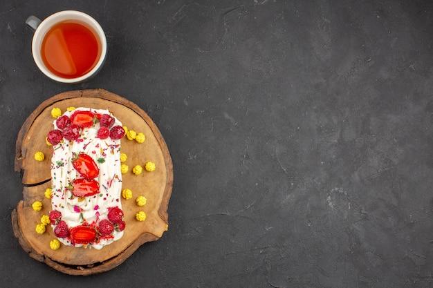 Draufsicht köstlicher cremiger kuchen mit früchten und tasse tee auf dunklem hintergrund keks-keks-kuchen süße tee-sahne-torte