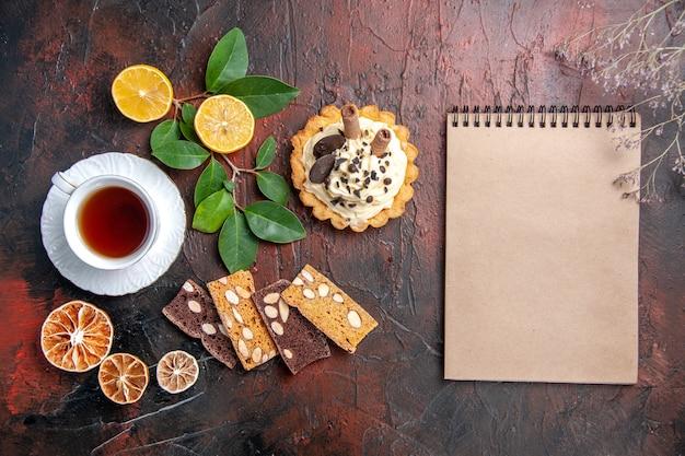 Draufsicht köstlicher cremiger kuchen mit tasse tee auf dem dunklen tisch süßer kuchen nachtisch