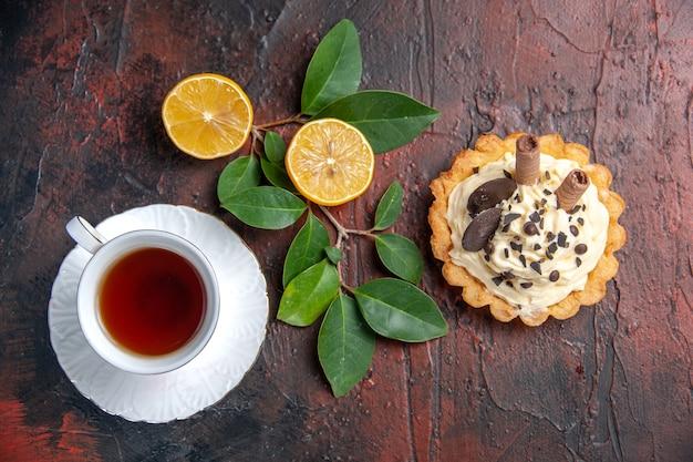 Draufsicht köstlicher cremiger kuchen mit tasse tee auf dem süßen nachtisch des dunklen tischkuchens