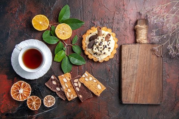 Draufsicht köstlicher cremiger kuchen mit tasse tee auf dunklem boden süßer kuchen nachtisch