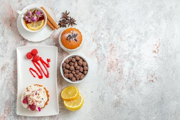 Draufsicht köstlicher cremiger kuchen mit tasse tee und zitronenscheiben auf weißem hintergrund keks sahnekuchen tee süßigkeiten