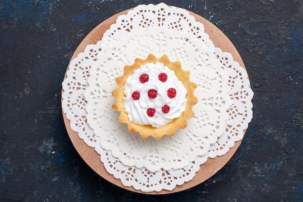 Draufsicht köstlicher d kuchen mit sahne und roten früchten auf dem dunkelblauen oberflächenkuchenfruchtkeks