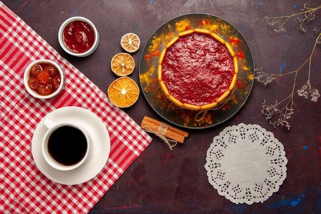 Draufsicht köstlicher dessertkuchen mit tasse kaffee und fruchtmarmeladen auf dunklem schreibtischkekszuckerplätzchkuchen-nachtisch süß