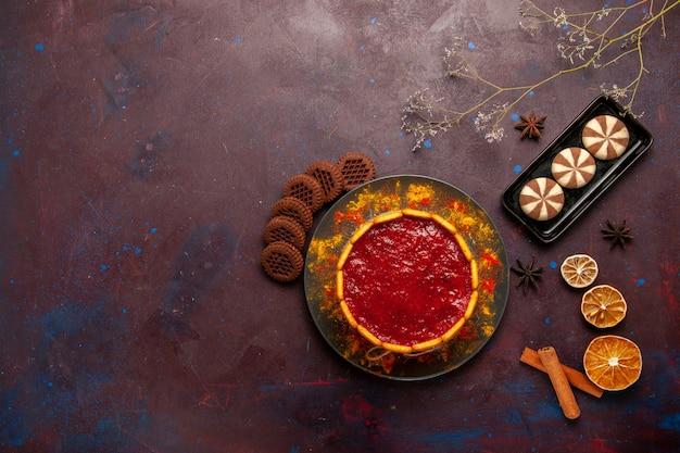 Draufsicht köstlicher dessertkuchen mit tasse kaffee und schokoladenplätzchen auf dem dunklen schreibtischkekszuckerplätzchen-kuchendessert süß