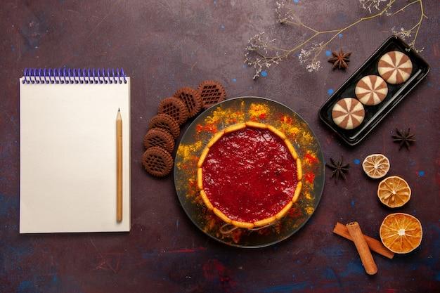 Draufsicht köstlicher dessertkuchen mit tasse kaffee und schokoladenplätzchen auf dunklem hintergrundkekszuckerplätzchenkuchen-dessert süß