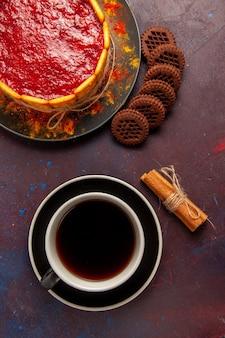 Draufsicht köstlicher dessertkuchen mit tasse kaffee und schokoladenplätzchen auf dunkler oberfläche kekszuckerplätzchen-kuchen-dessert süß
