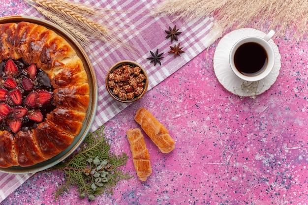 Draufsicht köstlicher erdbeerkuchen fruchtiger kuchen mit tasse tee auf dem rosa