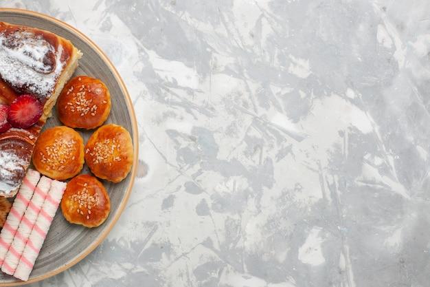 Draufsicht köstlicher erdbeerkuchen mit keksen und kleinen kuchen auf weißem schreibtischkekszuckerkuchen süßem kuchenplätzchen Kostenlose Fotos
