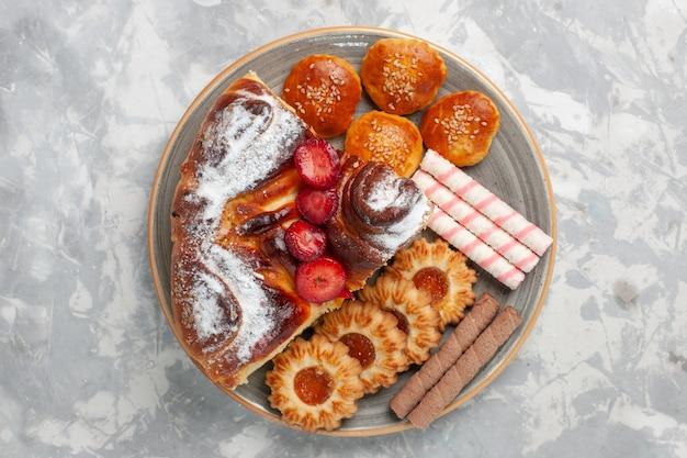 Draufsicht köstlicher erdbeerkuchen mit keksen und kleinen kuchen auf weißer oberfläche kekszuckerkuchen süßer kuchenplätzchen