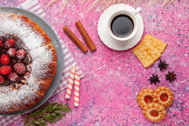 Draufsicht köstlicher erdbeerkuchen mit tasse teecrackern und auf rosafarbener oberfläche