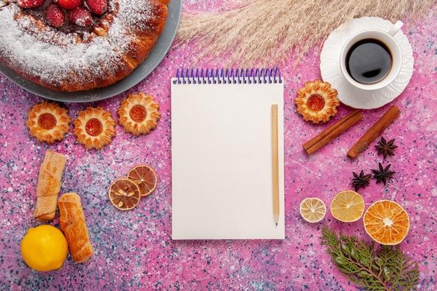 Draufsicht köstlicher erdbeerkuchenzuckerpulverkuchen mit keksen notizblock und tasse tee auf rosa hintergrundkuchen süßer zuckerplätzchenkuchen