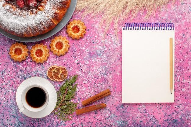 Draufsicht köstlicher erdbeerkuchenzuckerpulverkuchen mit keksnotizblock und tasse tee auf rosa hintergrundkuchen süßer zuckerplätzchenkuchen