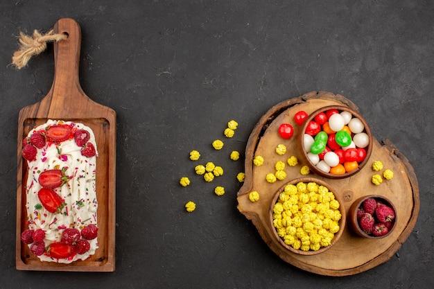 Draufsicht köstlicher fruchtiger kuchen mit bonbons auf dunklem hintergrund kandiszuckerkuchen-keks-teig-frucht