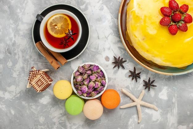 Draufsicht köstlicher fruchtiger kuchen mit gelben sirup französischen macarons und tasse tee auf weißem oberflächenkuchenkeks süßer zucker backen teekeks