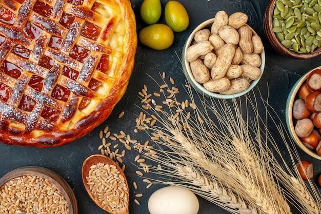 Draufsicht köstlicher fruchtiger kuchen mit nüssen auf dunklem keksplätzchen backen nusskuchen kuchen dessertfarbe tee