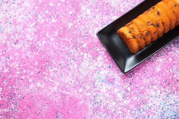Draufsicht köstlicher gebackener kuchen innerhalb der schwarzen kuchenform auf dem rosa schreibtisch.