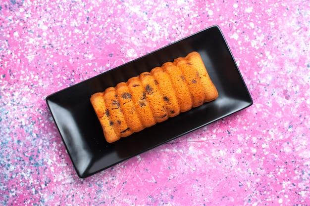 Draufsicht köstlicher gebackener kuchen innerhalb der schwarzen kuchenform auf rosa boden.