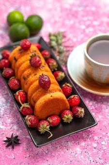 Draufsicht köstlicher gebackener kuchen innerhalb der schwarzen kuchenform mit frischem roten erdbeertee und zitronen auf dem rosa schreibtisch.