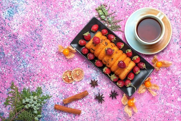 Draufsicht köstlicher gebackener kuchen innerhalb der schwarzen kuchenform mit frischen roten erdbeeren und einer tasse tee auf dem rosa schreibtisch.