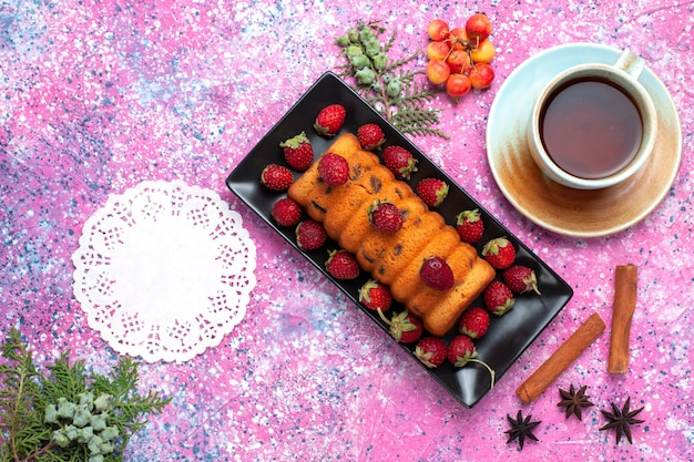 Draufsicht köstlicher gebackener kuchen innerhalb der schwarzen kuchenform mit frischen roten erdbeeren und tee auf dem rosa schreibtisch.