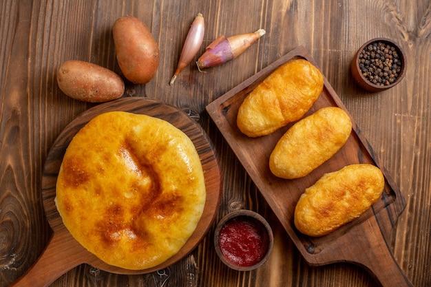 Draufsicht köstlicher gebackener kuchen mit kartoffelpüree innen und heißen kuchen auf hölzernem schreibtischkuchen heißer kuchenkuchen backen teigmahlzeit