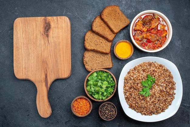 Draufsicht köstlicher gekochter buchweizen mit brot und suppe auf dunklem raum