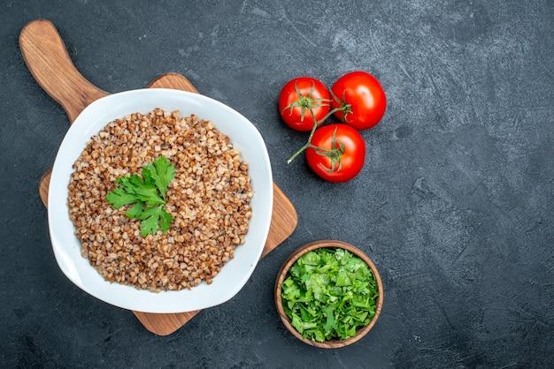 Draufsicht köstlicher gekochter buchweizen mit frischen tomaten und grüns auf dem grauen raum